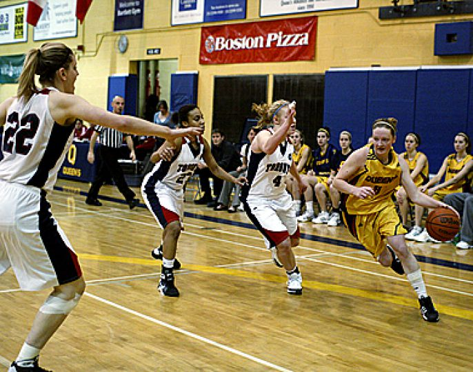Queen's guard Brittany Moore drives against U of T's Schutz (22) and Sherri Pierce Saturday. The Gaels lost 58-51.