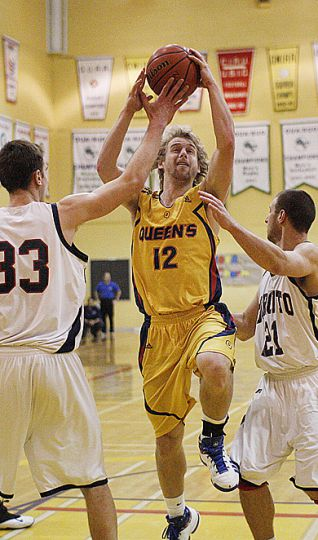 Queen's guard Ryan Hairsine drives against Drazen Glisic (33) and Patrick Sewell of the Varsity Blues Saturday.