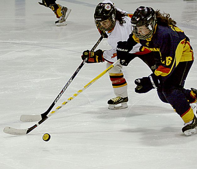 Queen's forward Becky Conroy battles Guelph's Stephanie Dykes for the puck Sunday at the Memorial Centre. The Gaels beat the Gryphons 3-1 with goals from Kelsey Thomson, Cassie Sparks and Amanda Morra.