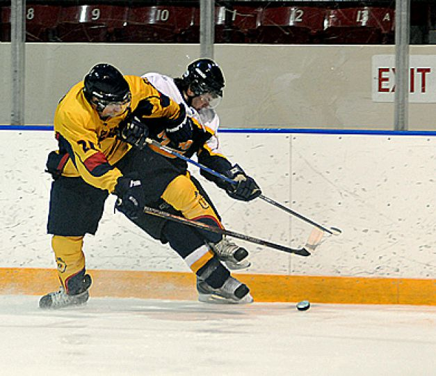 Queen's forward T.J. Sutter hits Ryerson's Michael Paolo Friday night at the Memorial Centre. The Gaels won 4-3.
