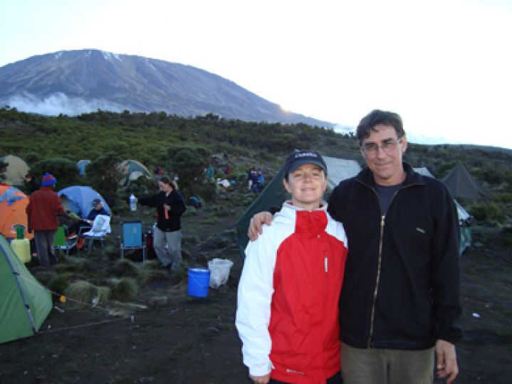 Queen's professors Dr. Karen Yeates and Gary Kibbins stand at the base of Mount Kilimanjaro.