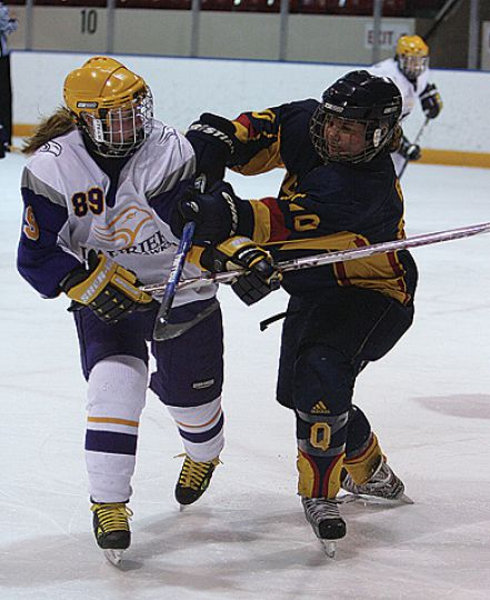Queen's defender Alison Bagg cross-checks Laurier's Katherine Shirriff Thursday.