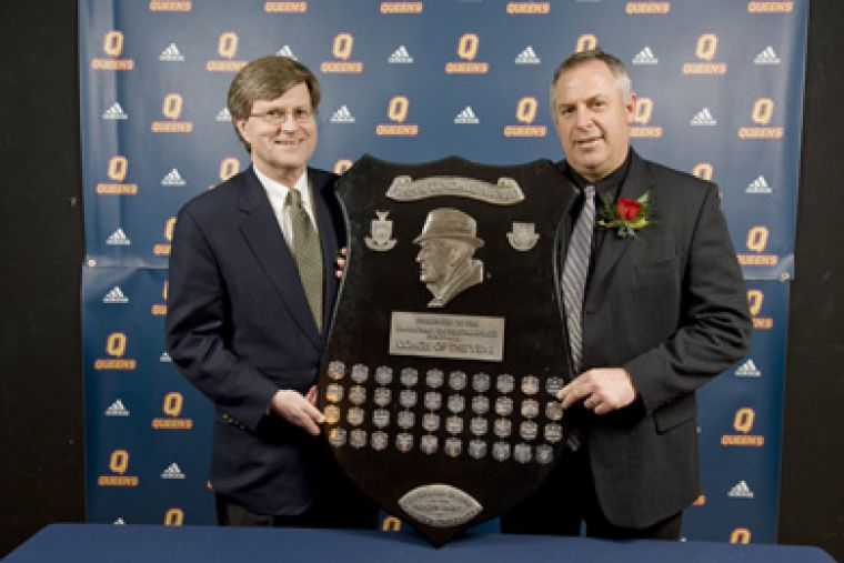 Football head coach Pat Sheahan (right) and acting vice-principal (advancement) Sean Conway pose with Sheahan's national coach of the year trophy Tuesday night.