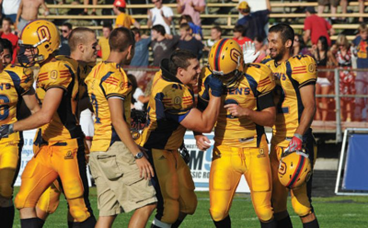 Queen's kicker Mike Petranovic is congratulated by his teammates after kicking the winning 37-yard field goal of the football team's dramatic season-opening win over the Guelph Gryphons on Monday afternoon. For full story, see page 22.