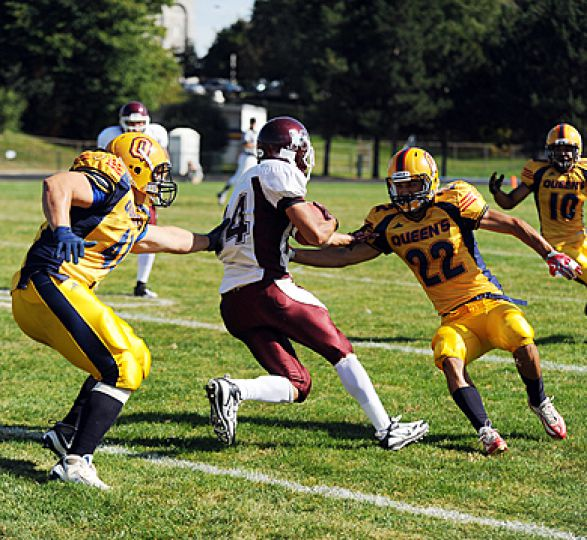 McMaster wide receiver tries to get past defensive back Rich Addison (22) and linebacker T.J. Leeper during Saturday's game at Richardson Stadium. The Gaels won 8-7.
