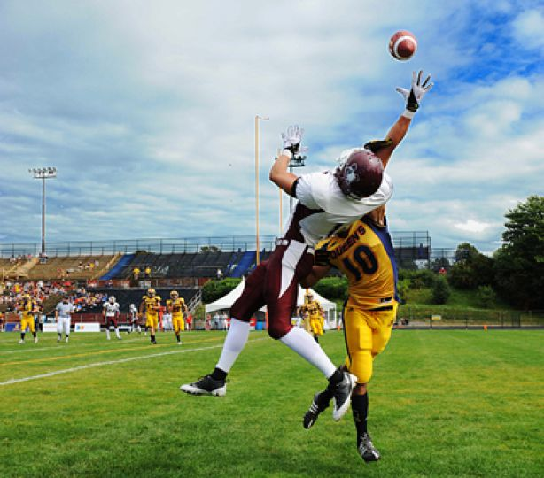 Marauder receiver Michael Dicroce leaps to make a catch against Queen's defensive back David Rooney.
