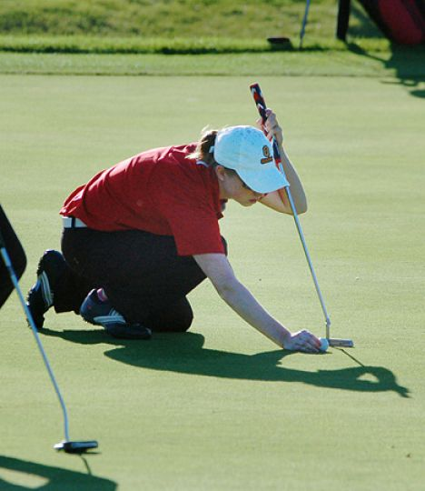 Women's team captain Kate Burnett sets the ball for a putt during the Queen's Invitational golf tournament last Sunday.