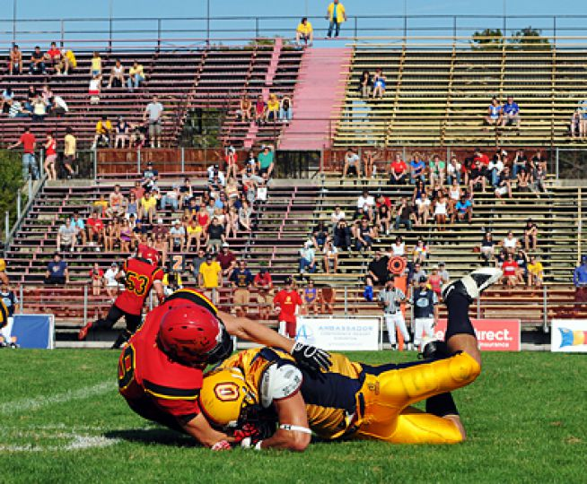 Gaels' tight end Christopher Ioannides tries to catch a pass in front of near-empty stands that were full just before halftime of Queen's nailbiting 52-49 win over Guelph on Sept. 7th.