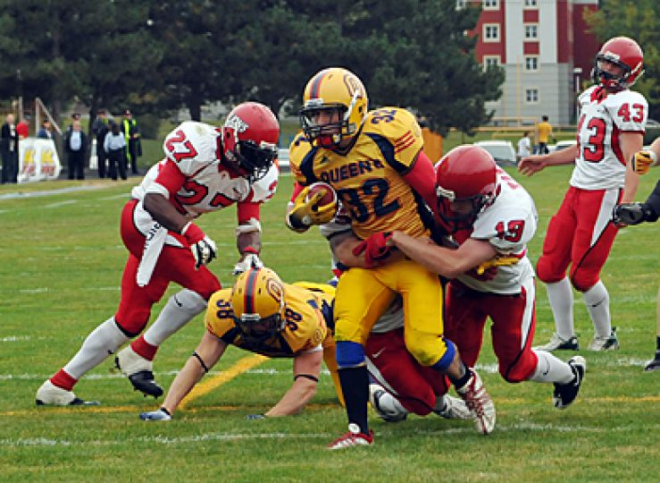 Running-back Ryan Granberg drags York defensive back Zach Thompson into the endzone with him for a Queen's touchdown.
