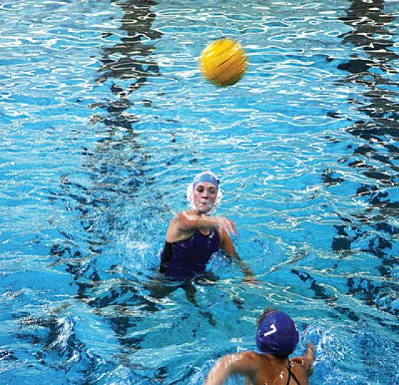 A water polo player rises out of the water to make a pass.