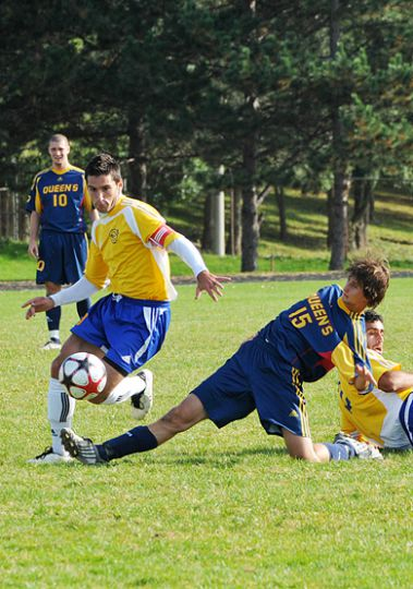 Queen's striker Adrian Rochford goes in for a tackle against Rams midfielder Alex Bratelic Sunday at Richardson Stadium.