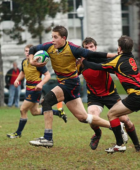 First-year scrum half Liam Underwood stiff arms a Guelph defender en route to scoring a try during Friday's convincing 31-5 win over the Guelph Gryphons at Kingston Field.