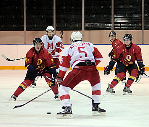 McGill captain Yan Turcotte winds up a slapshot while Gaels' forwards Jeffrey Johnstone and T.J. Sutter set up to block it.