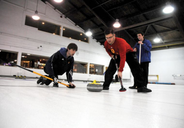 The curling team's David Durant lets go of a rock as Mackenzie Dixon begins sweeping.