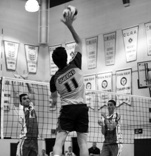 Outside Brett Walter spikes during Queen's straight-set victory over RMC.