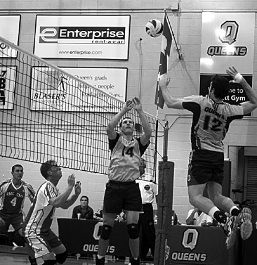 Setter Jackson Dakin puts the ball up for middle Anthony Pitfield to spike on Friday at Bartlett Gym.
