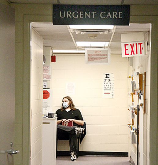A student wearing a face mask waits in the flu-assessment clinic at Student Health Services.