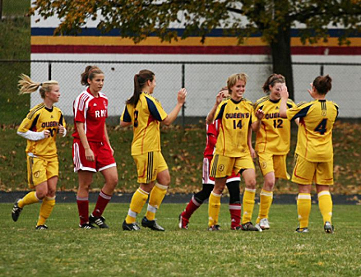 The women's soccer team celebrates striker Renée MacLellan's (#14) 11th goal of the season during Queen's 5-0 win over the Royal Military College Paladins on Oct. 21 at Richardson Stadium.