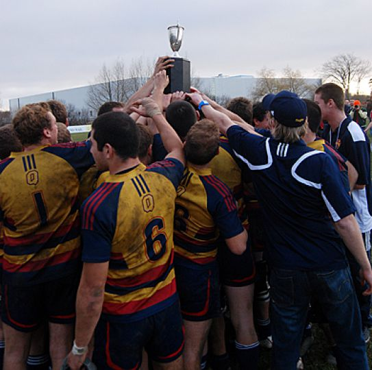 The men's rugby team crowds around the Turner Trophy after their 23-19 finals win over the Western Mustangs on Saturday.