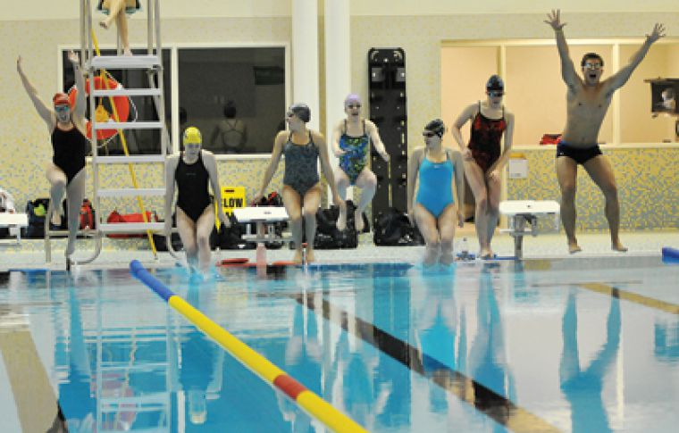Students jump into the 14-lane pool in the new Athletics and Recreation Centre early Tuesday morning.