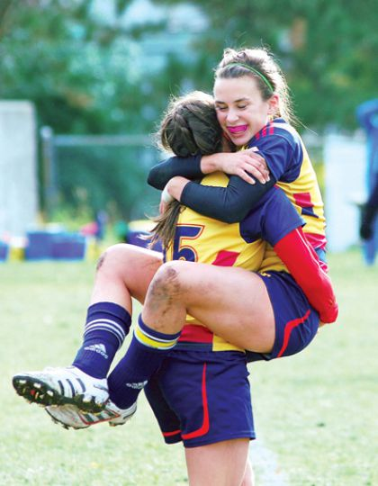 The women's rugby team celebrates their 15-8 win over the Waterloo Warriors in Kingston.