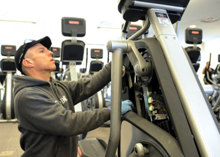 Currently there are three broken ellipticals and two broken treadmills in the ARC. National Fitness Products staff member James Hunter assesses the condition of an elliptical.