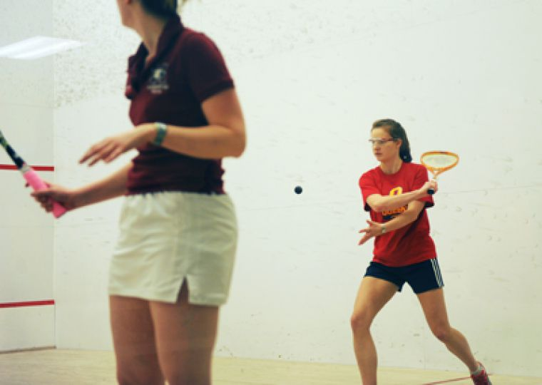 Women's number one player Erin Roberts puts the ball back in play against a McMaster opponent.