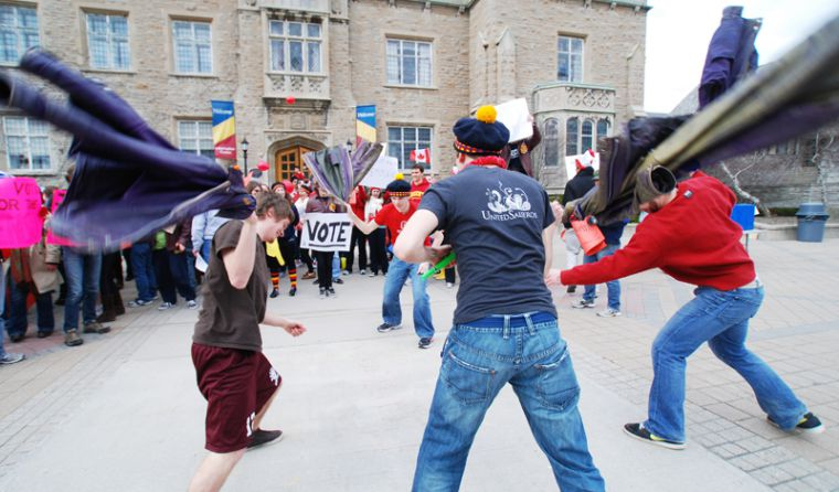 Engineering students slam their faculty jackets outside of the John Deustch University Centre during the Queen's University Vote Mob.