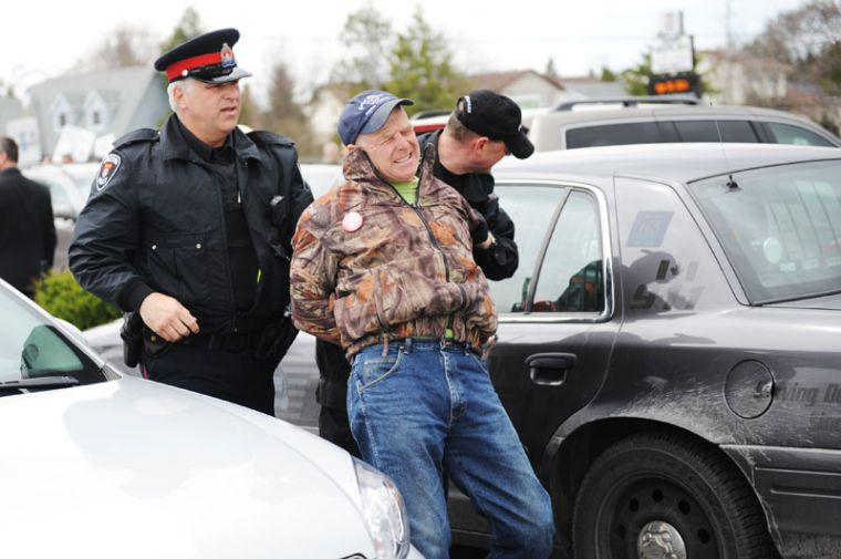 Protester Jeff Peters cries out as he is restrained by Kingston Police officers following his arrest Friday afternoon.