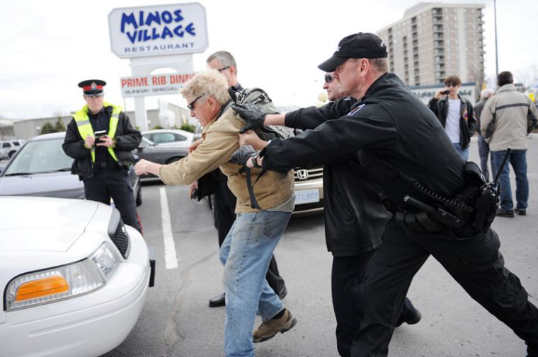 Kingston police arrest a protester before the start of the Kingston Conservative rally.