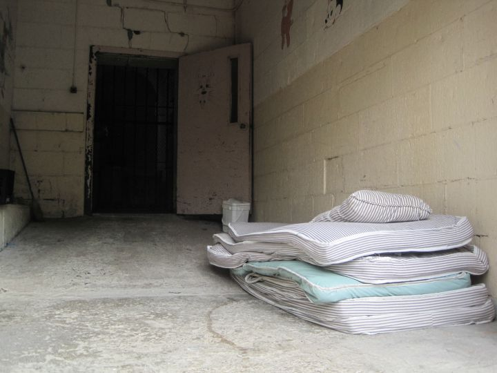 Old mattresses wait on a loading dock for disposal.
