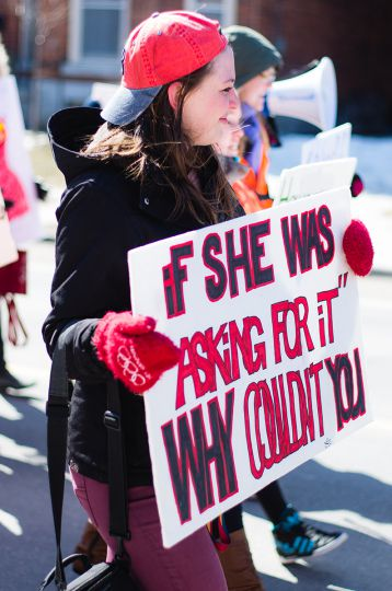 "A marcher holds a sign questioning the argument that a victim of sexual assault is ""asking for it""."