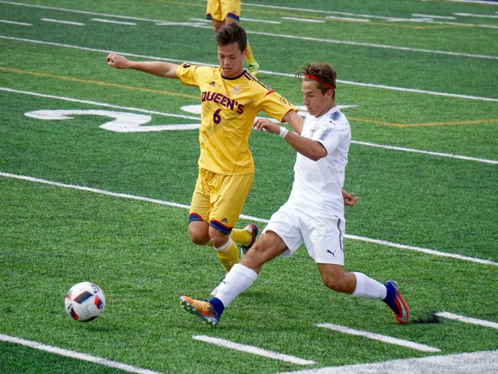 Queen's midfielder Michael Chang challenges a defender in the first half.