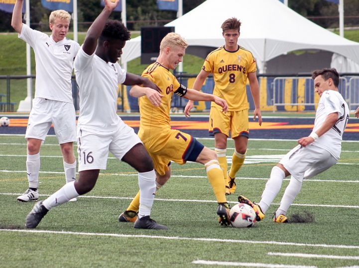 A pair of Carleton defenders try to slow down Gaels forward Jacob Schroeter as he shifts past them.
