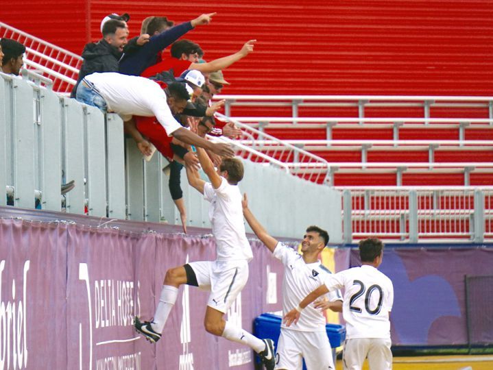 A group of Carleton players celebrate with the team's travelling fans after going up 1-0.