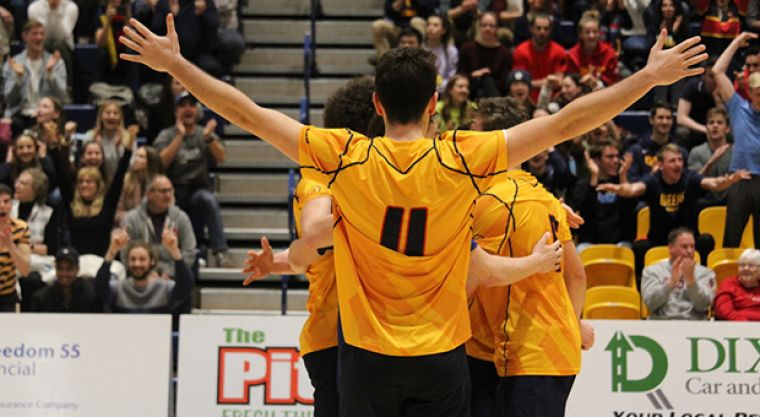 First-year Adam Boljkovak celebrates with teammates after winning a big point in the fifth set.