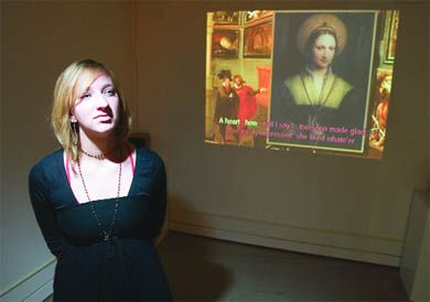 Lisa Visser, BFA '06, stands in front of a multimedia work created by Modern Fuel members Tony Leamon and Vincent Perez.