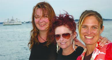Wolfe Island Music Festival organizers Virginia Clark, Tanis Rideout and Sarah McDermott on the waterfront with the Wolfe Island Ferry in the background.