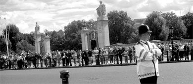 A London police officer stands guard while hundreds of tourists line the streets of Buckingham Palace and watch the Changing of the Guard.