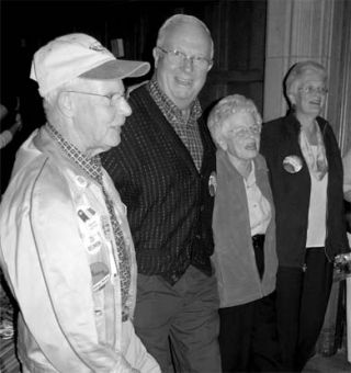 "Bands alumnus Bob Burnside, Sci '56 (at left), and his wife Doris (second from right) join fellow ""Bandsies"" in a rousing Oil Thigh at the Bands' centennial celebration Friday night."