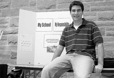 Jon Sinclair, Comm '06, sits in front of one of the booths that raised $2,000.