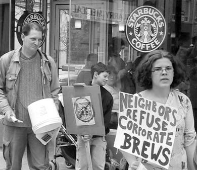 Professor Richard Day, far left, and Grace Laing, far right, protest Starbucks' Grand Opening on Saturday.