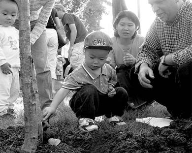 A day care goer plants a tree to wish the Day Care Centre a happy birthday.