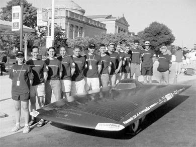 The Solar Car team, standing by Mirage, prepares to race in the American Solar Challenge