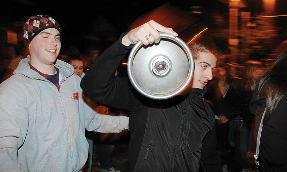 Two partiers take a detour for a refill on Aberdeen Street Saturday night. Police estimate between 4,000 and 6,500 people were on the street that night.