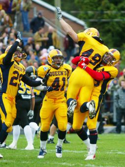 The Gaels' defence celebrates their Homecoming win over Waterloo.