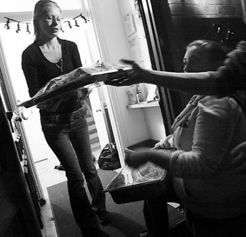 A Kingston Youth Shelter volunteer accepts food from Sheri Krell, co-chair of Soul Food, on Monday night.