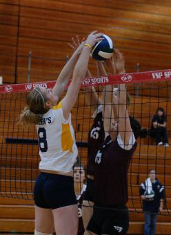 Gaels' right-side hitter Lisa Cooke blocks an Ottawa attacker in Friday's game.