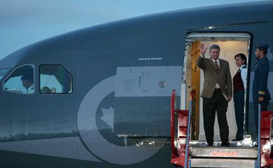 Canada's Prime Minister Stephen Harper waves to journalists upon his arrival at a military airport in Bogota, Colombia, Sunday, July 15, 2007.