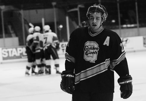 Queen's forward T.J. Sutter looks forlorn as the Redmen celebrate in the background Saturday night at the Memorial Centre.